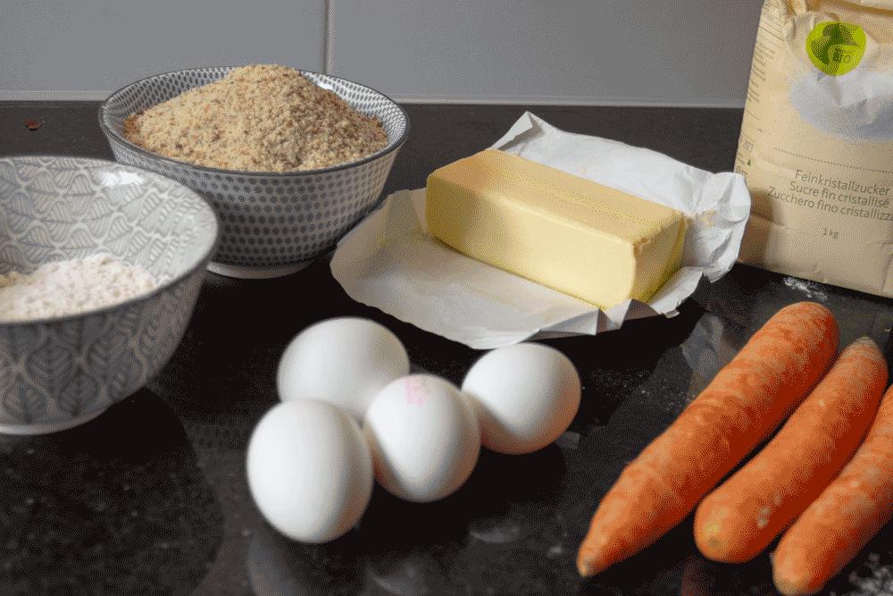 Eier, Butter, Rüebli, Mehl, Zucker und gemahlene Mandeln als Zutaten für den Rüeblikuchen.